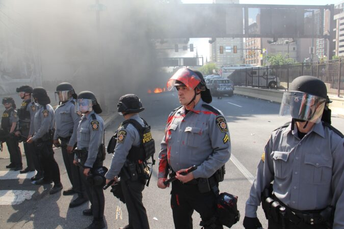 Pennsylvania state troopers keep protesters away from a burning car and vandalized police cars at Broad and Vine streets. (Emma Lee/WHYY)