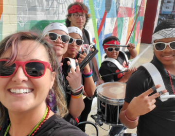 South Philadelphia High School music director Courtney Powers, left, with her students outside the school building earlier this school year. (Courtesy of Courtney Powers)