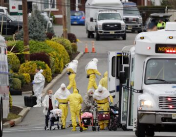 Residents from St. Joseph's Senior Home are helped on to buses in Woodbridge, N.J., Wednesday, March 25, 2020. More than 90 residents of the nursing home were transferred to a facility in Whippany after several tested positive for COVID-19. (AP Photo/Seth Wenig)