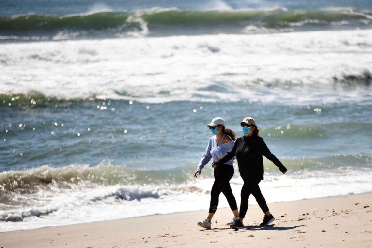 People wearing a protective face masks as a precaution against the coronavirus walk on the beach in Belmar, N.J., Saturday, May 2, 2020. (AP Photo/Matt Rourke)