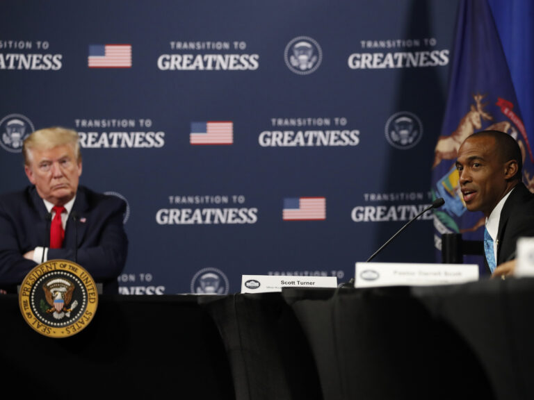 President Trump listens as Scott Turner, executive director of the White House Opportunity and Revitalization Council, speaks during a meeting with African American leaders in Michigan on Thursday. (Alex Brandon/AP Photo)