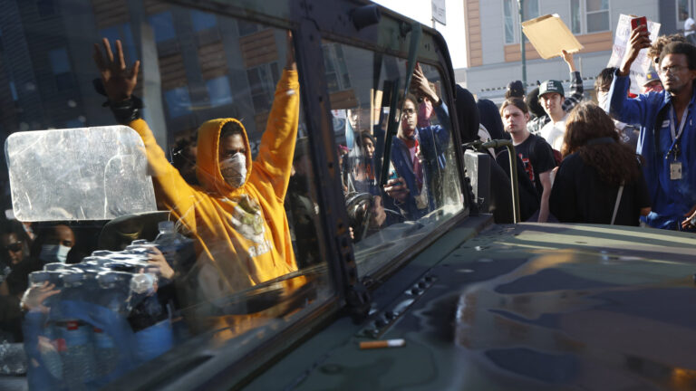 A National Guard vehicle reflects a crowd of protesters Friday in Minneapolis, where Maj. Gen. Jon Jensen said that night's deployment