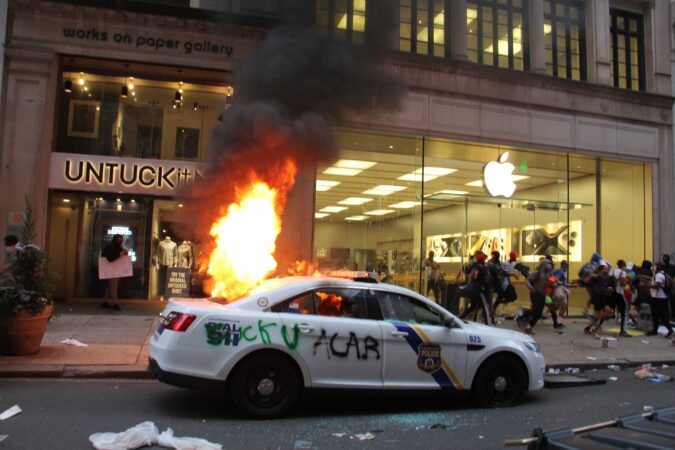 A police car burns outside a looted Apple store in Center City.