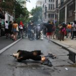 A mannequin burns in the street as looters make their way through Center City.