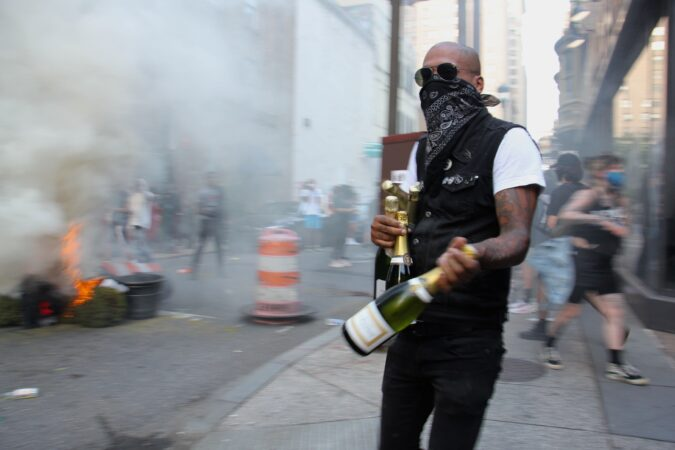 A looter leaves Marathon bar at 16th and Samson with arms full of champagne