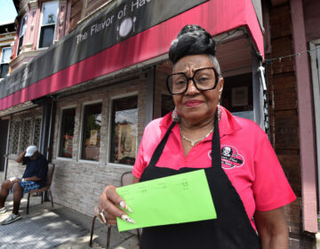On June 5, Corinne Bradley-Powers, owner of Corinne's Place, stands in front of her popular Camden restaurant holding the notice she received that her restaurant would be on a list for sheriff's sale this month if she didn't pay the $282 she owed.  (Photo by April Saul for WHYY)