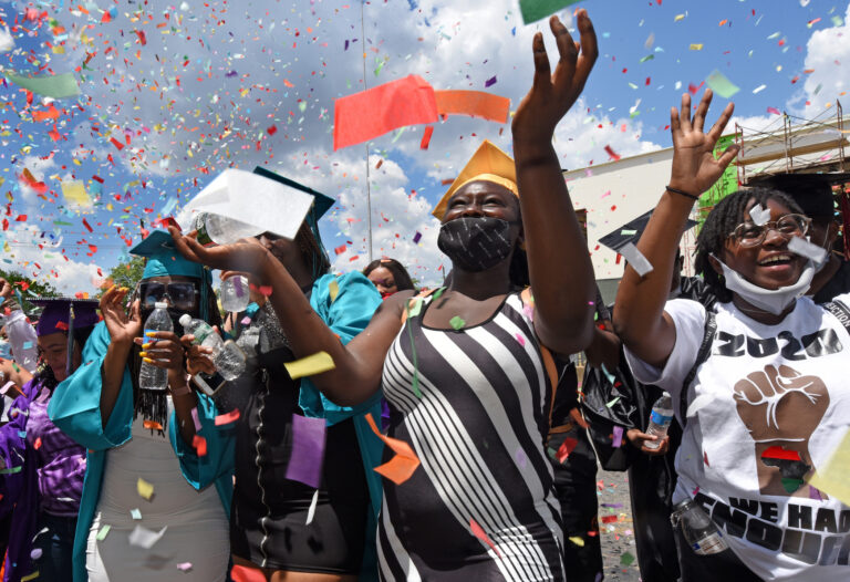 At Farnham Park on June 26, Camden High graduate Zanabria Harris, 18, stands in a sea of confetti at the end of the parade.  (Photo by April Saul for WHYY)