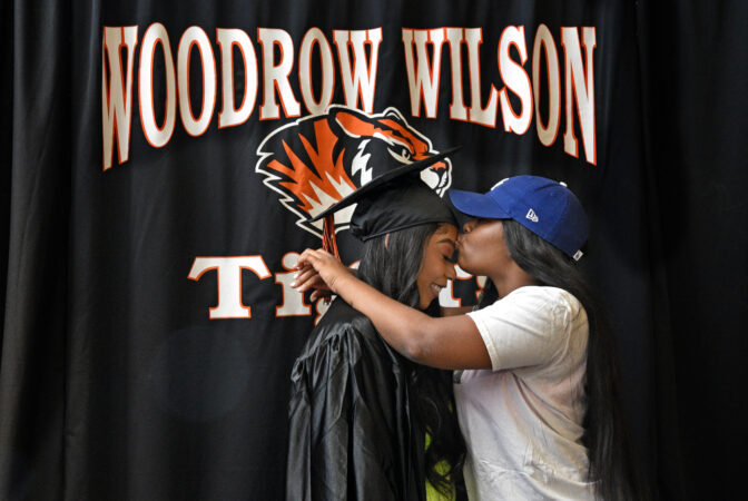 At Woodrow Wilson HS on June 24, graduate Domera Nunn gets a kiss from sister Quadire Wilson during a photo shoot. Nunn, who is headed for Rutgers in New Brunswick in the fall, said,