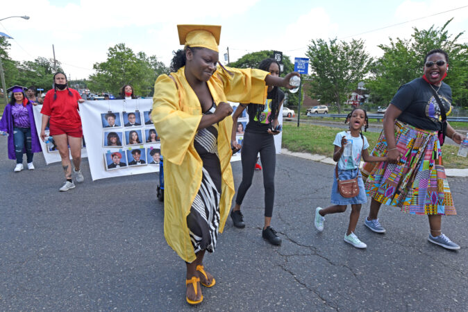 During the parade on June 26, Camden High graduate Zanabria Harris, 18, dances on Baird Boulevard; at right is parade organizer Ronsha Dickerson. (Photo by April Saul for WHYY)