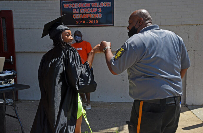 At Woodrow Wilson HS on June 24, graduate Damera Nunn fist-bumps a security officer on her way to pose for graduation photos.  (Photo by April Saul for WHYY)