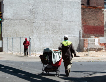 A person walks with their belongings on Kensington Avenue on May 7, 2020. (Erin Blewett / Kensington Voice)