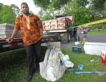 Pastor Levi Combs III of Camden's First Refuge Baptist Church, watches over pieces of the Christopher Columbus statue in Farnham Park on Friday, June 12, 2020. (April Saul for WHYY)