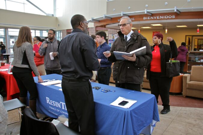 Job seekers line up at the ResinTech table during a job fair