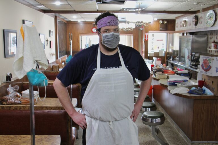 Chad Todd stands in the dining room at Sulimay's restaurant, which has become a staging area. (Emma Lee/WHYY)