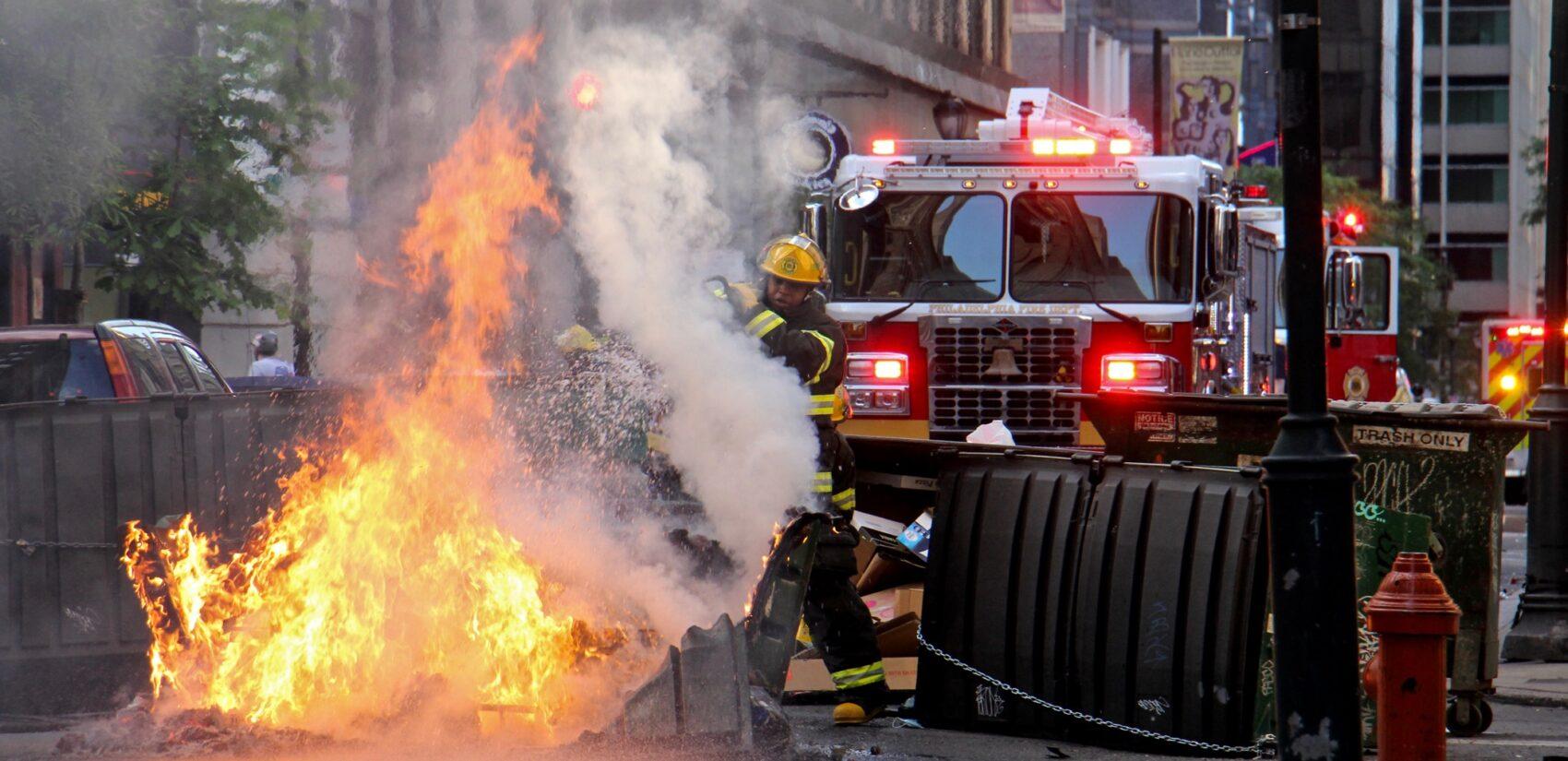 A Philadelphia firefighter puts out a dumpster fire
