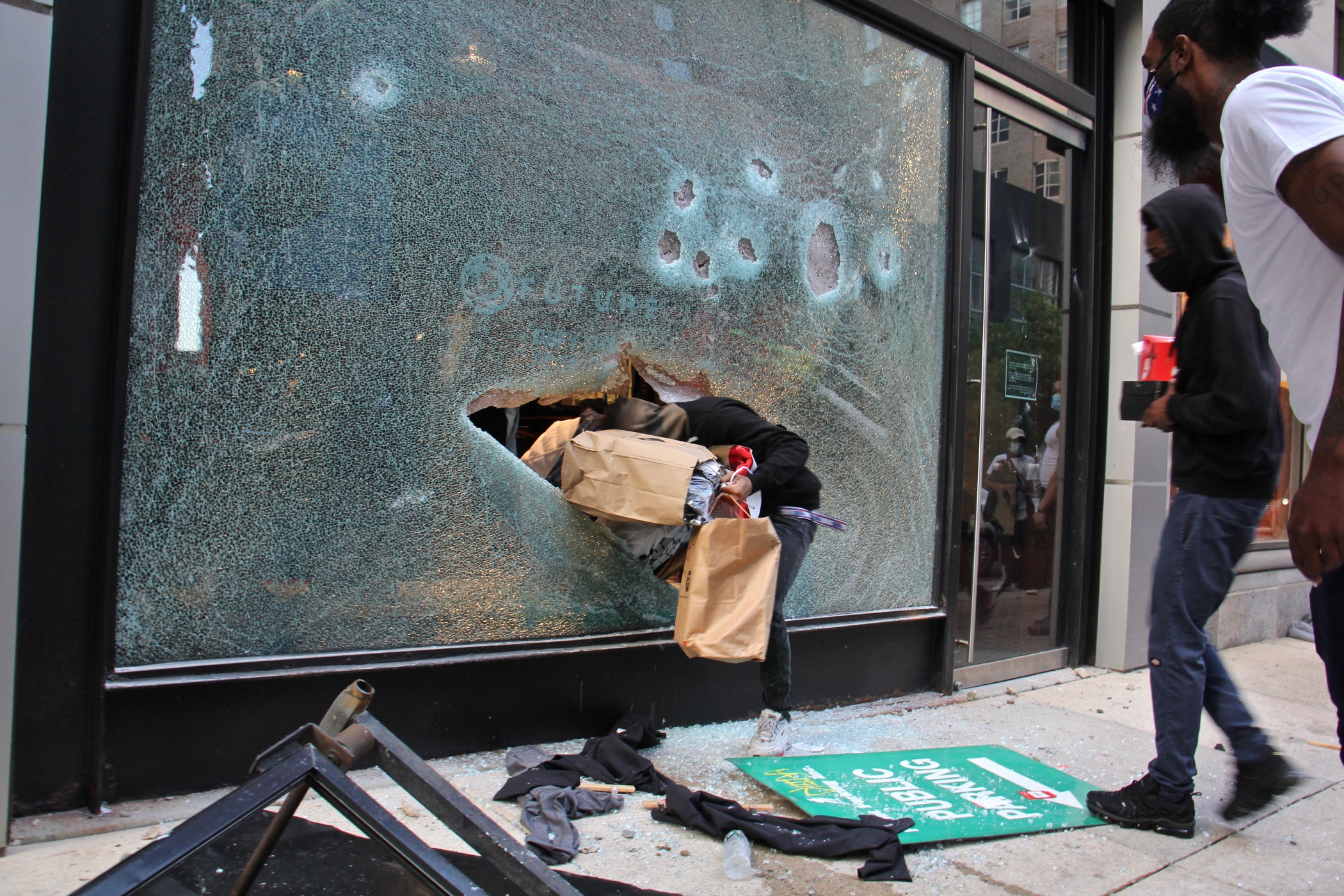 A looter emerges from the shattered window of a North Face store