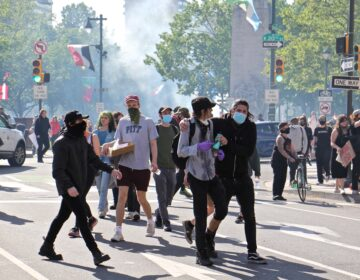 Protesters flee a cloud of tear gas