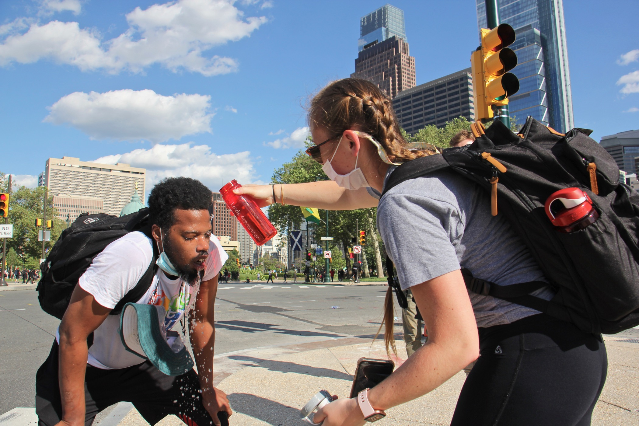 Protesters help each other after being tear-gassed