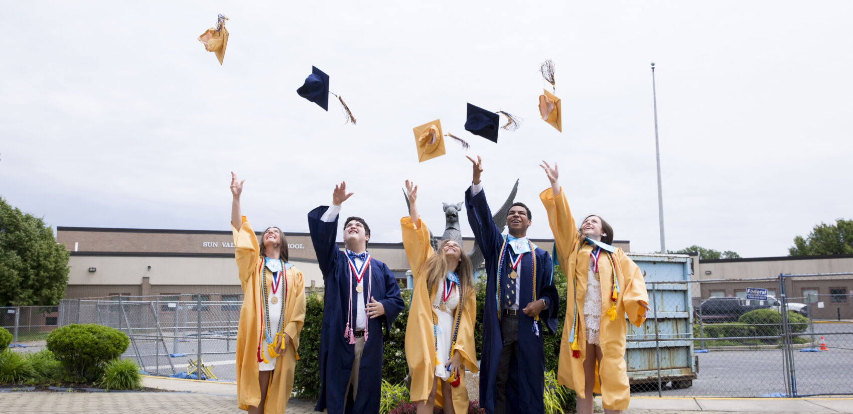 Bryson Eldridge (second to right), senior class president at his school, throws his graduation cap with other class officers after a segment they recorded for virtual graduation. Sun Valley High, in the Penn-Delco School District, is about 80% white.  (Rachel Wisniewski for Keystone Crossroads)