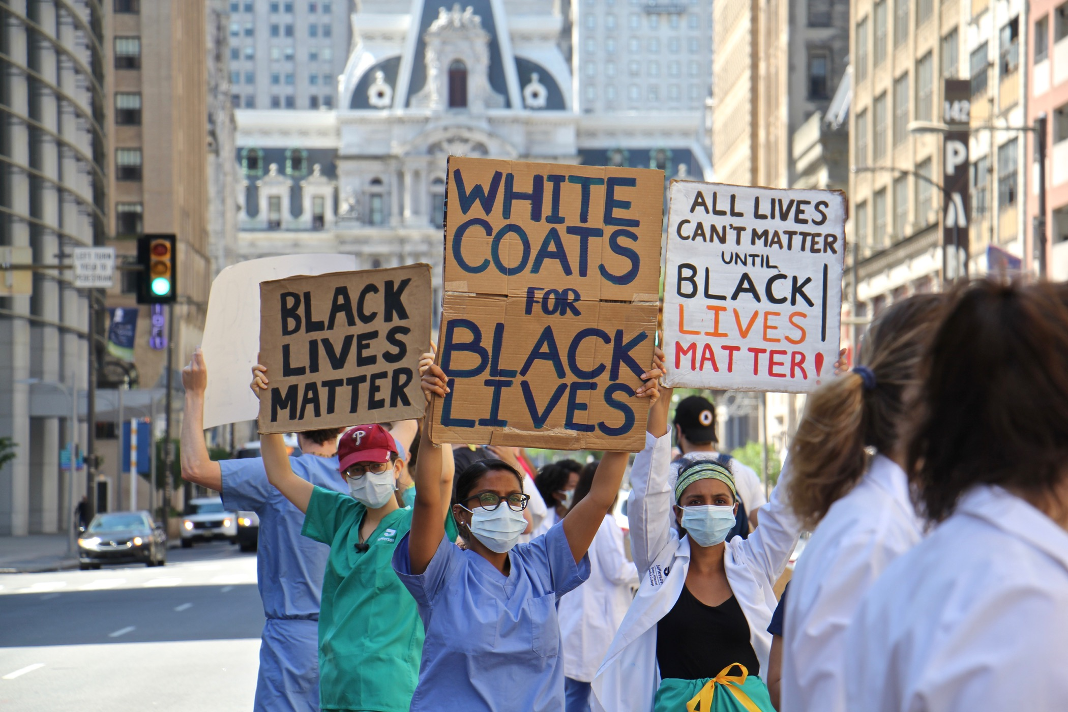 Protesters in scrubs and lab coats