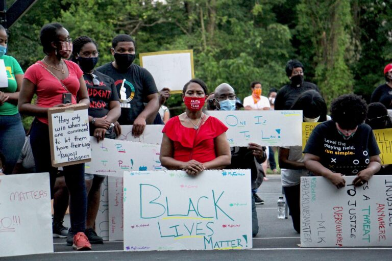 Protesters kneel for 8 minutes and 46 seconds in remembrance of George Floyd during a Black Lives Matter rally at Linconia Park in Bensalem, Pa. Floyd was killed in Minneapolis police custody by an officer who kneeled on his neck, sparking protests in cities and towns across the country. (Emma Lee/WHYY)
