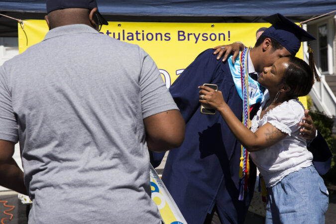 Bryson receives congratulations from his parents, Elaina and Greg, after receiving his high school diploma via a modified graduation ceremony on June 9, 2020. (Rachel Wisniewski for Keystone Crossroads)