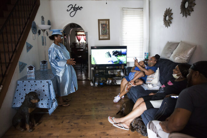 Family members take photos of Aliah as she prepares for her high school's virtual graduation ceremony at her father's house in the Grays Ferry section of Philadelphia. (Rachel Wisniewski for Keystone Crossroads)