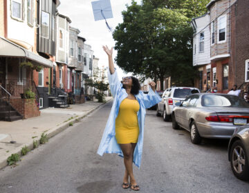 Aliah Harris, 18, throws her graduation cap in celebration on her dad's South Philly block on June 10, 2020. (Rachel Wisniewski for WHYY)