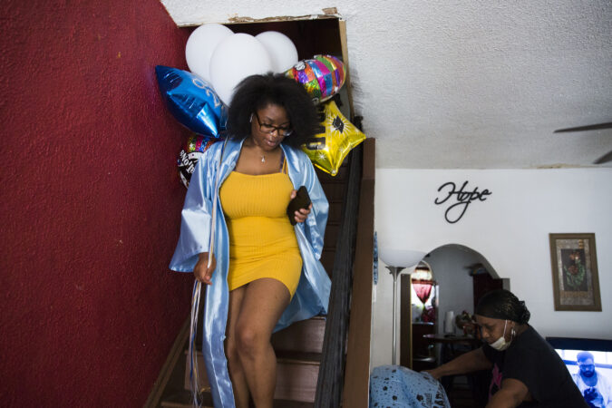 Aliah brings graduation themed balloons downstairs while her grandmother, Toni Carter, sets up a decorated table in the family's living room. (Rachel Wisniewski for Keystone Crossroads)