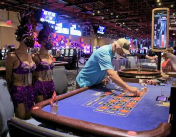 Bob Mills of Wenonah, N.J., places a bet at Harrah's Philadelphia, attended by showgirls Vanessa Harkins and Angel Simpkins. (Emma Lee/WHYY)