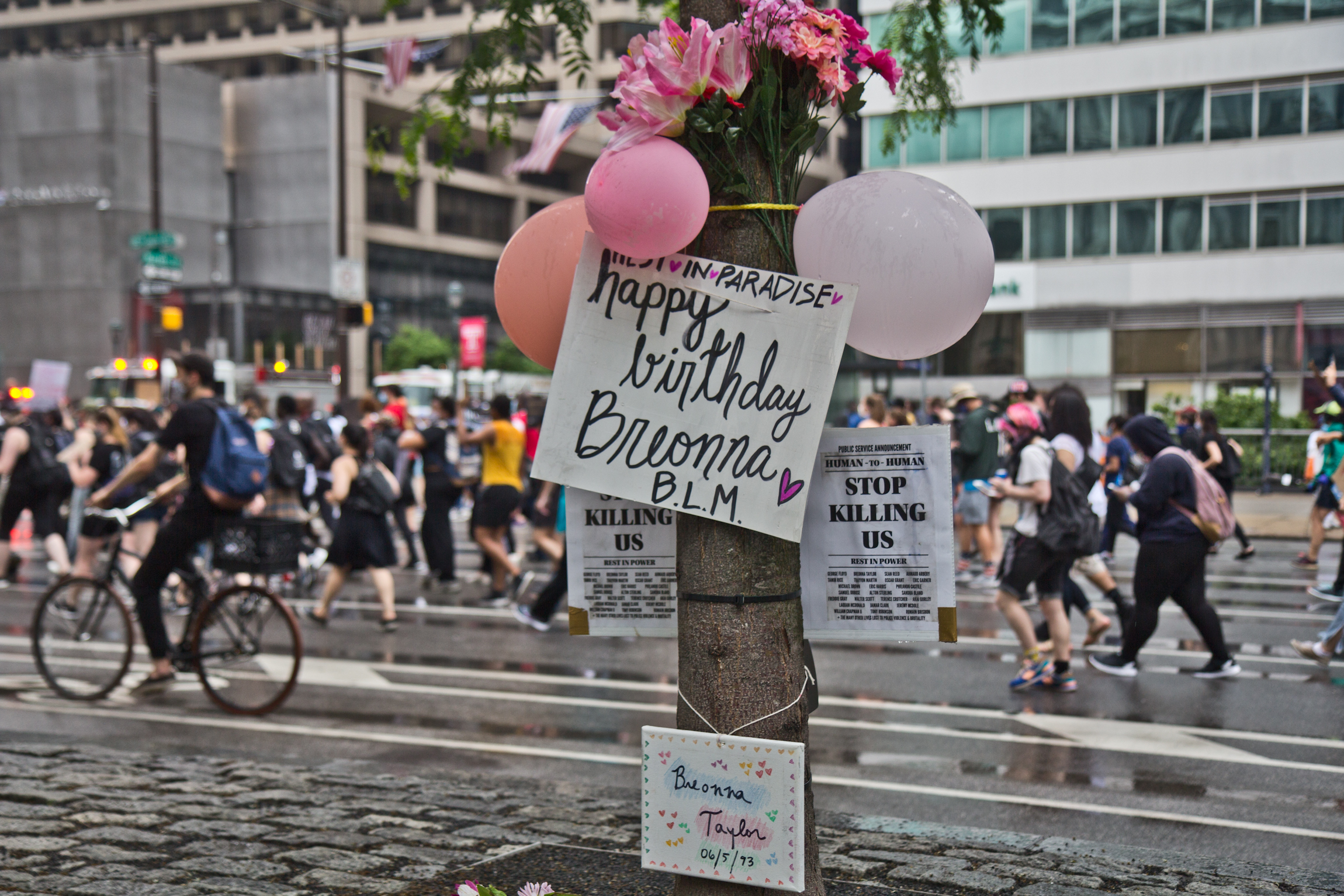 Protesters march by a tree decorated in honor of Breonna Taylor