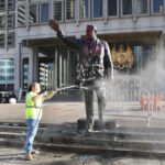 A worker power washes the Frank Rizzo statue in front of the Municipal Services Building on Sunday. (Bradley Maule for PlanPhilly)