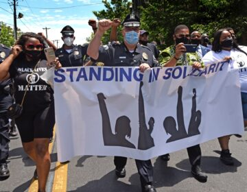Camden County Metro Police Chief Joe Wysocki raises a fist while marching with Camden residents and activists on May 30, 2020 to protest the killing of George Floyd in Minneapolis. (Photo by April Saul via AP)