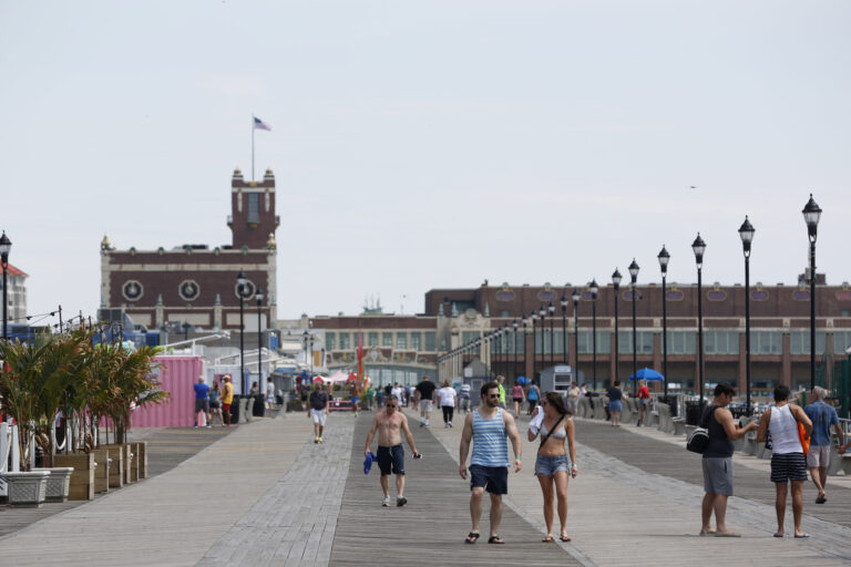 People walk along the boardwalk in Asbury Park, N.J., Wednesday, June 21, 2017. (AP Photo/Seth Wenig)