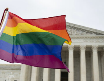 Supporters of the LGBT wave their flag in front of the U.S. Supreme Court, Tuesday, Oct. 8, 2019, in Washington. (AP Photo/Manuel Balce Ceneta)