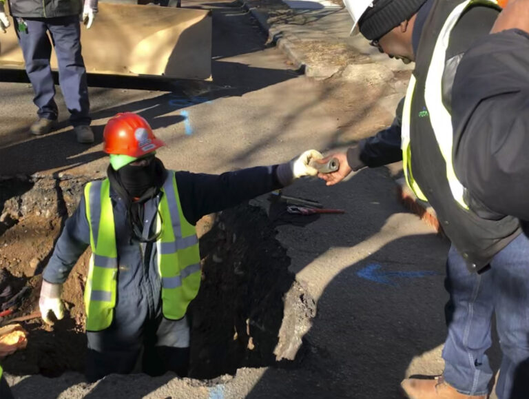 A worker hands a piece of lead pipe to a colleague as they work to remove water service lines Thursday, Jan. 9, 2020 in Trenton, N.J. The city announced it is replacing 37,000 lead pipes over five years as part of an an effort to remove the potentially harmful pipes. (AP Photo/Mike Catalini)