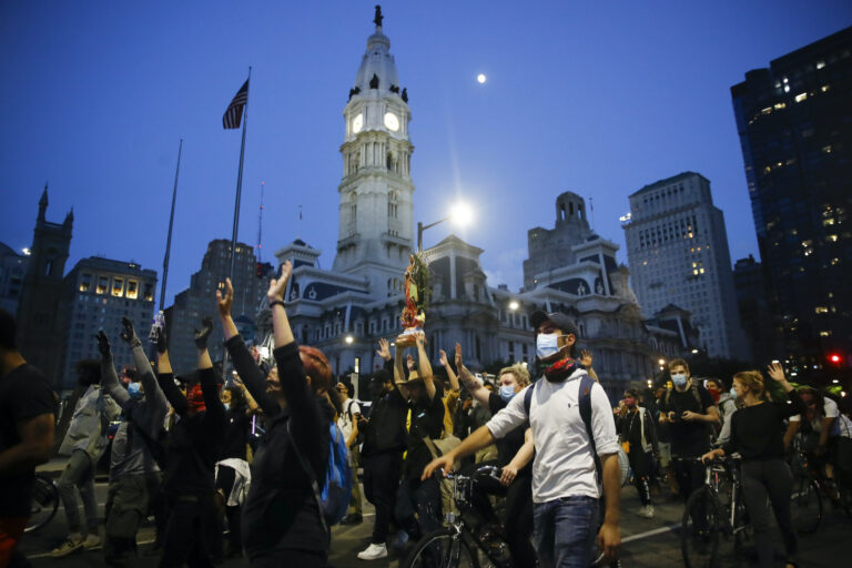 Demonstrators march Tuesday, June 2, 2020, near City Hall in Philadelphia, during a protest over the death of George Floyd, who died May 25 after he was restrained by Minneapolis police. (AP Photo/Matt Rourke)