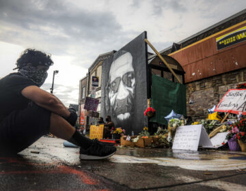 "After a new mural, center, of George Floyd is added to a growing memorial of tributes, Trevor Rodriquez sits alone at the spot where Floyd died while in police custody, Tuesday June 2, 2020, in Minneapolis, Minn.  ""I have been out every single night protesting peacefully, just trying to support everything,"" said Rodriquez. ""I didn't want to come here just on a rush, so I had to just take a moment to pay my respect.""  (AP Photo/Bebeto Matthews"