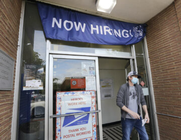 In this photo taken Thursday, June 4, 2020, a customer walks out of a U.S. Post Office branch and under a banner advertising a job opening, in Seattle. (Elaine Thompson/AP Photo)