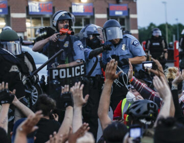 A police officer points a hand cannon at protesters who have been detained pending arrest on South Washington Street, Sunday, May 31, 2020, in Minneapolis. (AP Photo/John Minchillo)