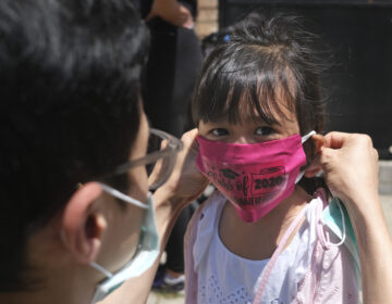 Olivia Chan's father helps her with new mask she received during a graduation ceremony for her Pre-K class in front of Bradford School in Jersey City, N.J., Wednesday, June 10, 2020. (AP Photo/Seth Wenig)