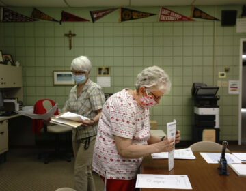 Guidance secretary Marge Berckmiller, left, and Sister Bridget Reilly, director of guidance, prepare student transcripts to send to other schools after the closure of Quigley Catholic High School in Baden, Pa., Monday, June 8, 2020. (AP Photo/ Jessie Wardarski)