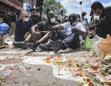 In this June 1, 2020 file photo, an emotional Terrence Floyd, second from right, is comforted as he sits at the spot at the intersection of 38th Street and Chicago Avenue, Minneapolis, Minn., where his brother George Floyd, encountered police and died while in their custody. (AP Photo/Bebeto Matthews File)