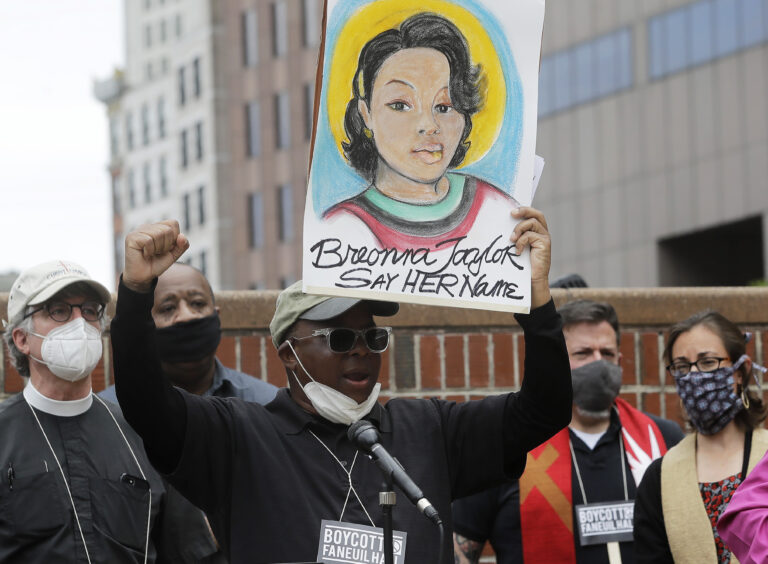 In this June 9, 2020, file photo, Kevin Peterson, center, founder and executive director of the New Democracy Coalition, displays a placard showing Breonna Taylor as he addresses a rally in Boston. (AP Photo/Steven Senne, File)