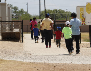 In this Aug. 23, 2019 file photo, immigrants seeking asylum hold hands as they leave a cafeteria at the ICE South Texas Family Residential Center in Dilley, Texas. (AP Photo/Eric Gay, File)