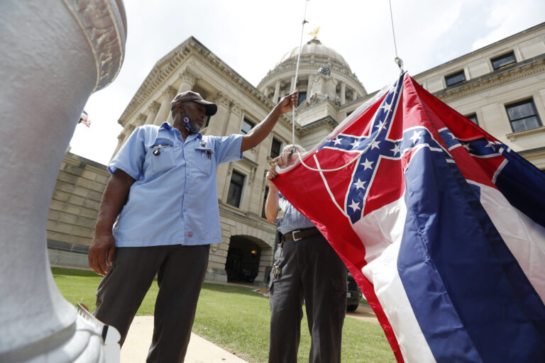 Mississippi Department of Finance and Administration employees Willie Townsend, left, and Joe Brown, attach a Mississippi state flag to the harness before raising it over the Capitol grounds in Jackson, Miss., Tuesday, June 30, 2020. (AP Photo/Rogelio V. Solis)