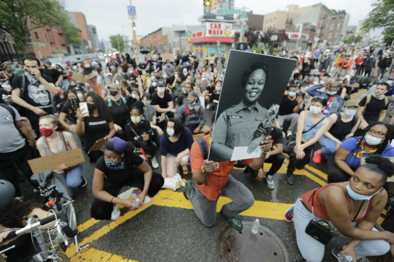 A man holds a photograph of Breonna Taylor on her birthday as he kneels with other protesters