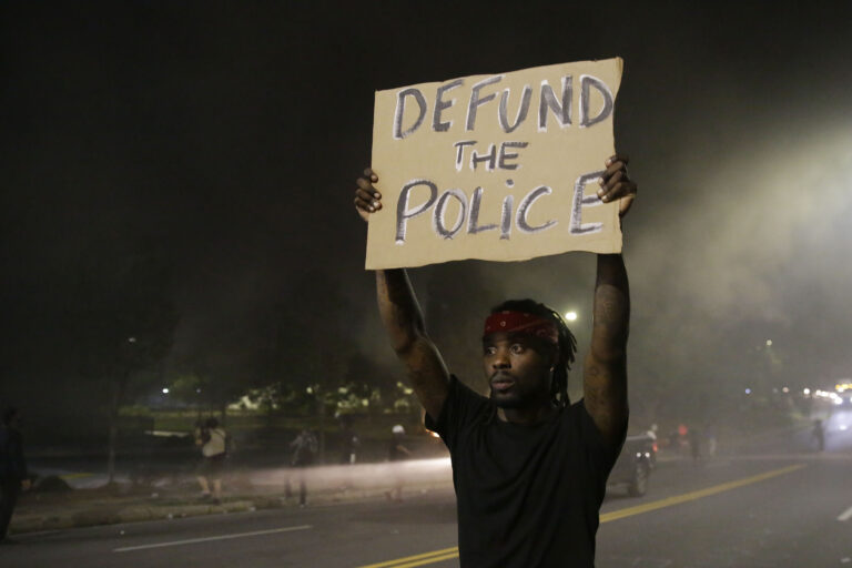 A man holds up a sign amid smoke of a fire during a protest