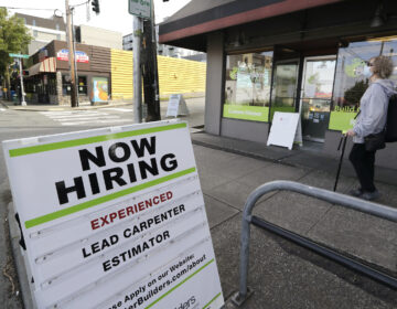 A pedestrian wearing a mask walks past reader board advertising a job opening for a remodeling company