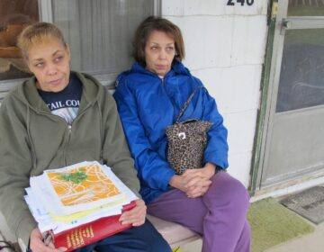 Jeanie Moten with her sister on their mother's porch in Rea, Pa. She holds a stack of medical records. The Motens say they received no help from DOH regarding their fracking health complaints. A case file released by the DOH through a Right-To-Know request confirmed that. (Susan Phillips / StateImpactPA)